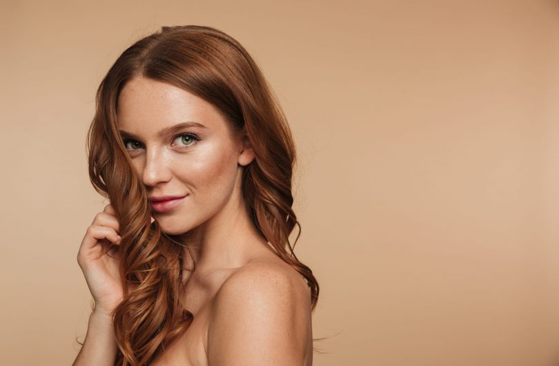 Beauty portrait of mystery smiling ginger woman with long hair posing sideways and looking at the camera over cream background